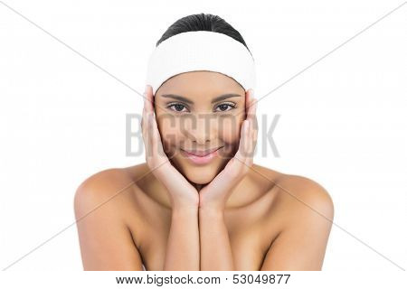 Happy nude brunette with hairband touching face on white background