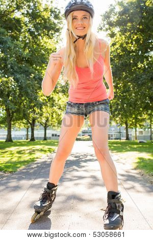 Casual happy blonde inline skating in a park