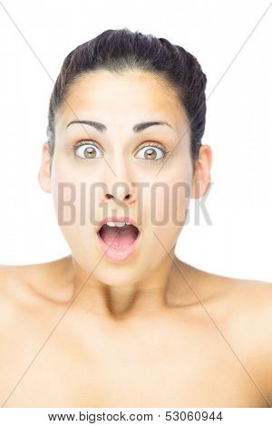Front view of astonished woman looking at camera on white background