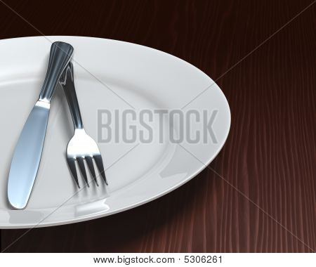 Clean Plate & Cutlery On Dark Woodgrain Table