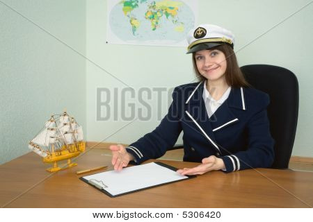 Girl In A Sea Uniform Sitting At A Table With A Tablet