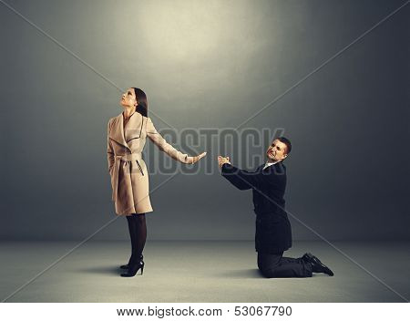 man standing on his knees and apologizing but woman refusing to him