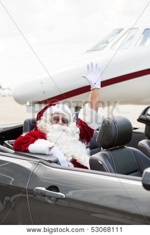 Portrait of Santa waving hand while sitting in convertible against private jet at airport terminal