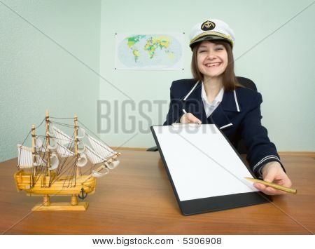 Woman In A Sea Uniform Sitting At A Table With A Tablet
