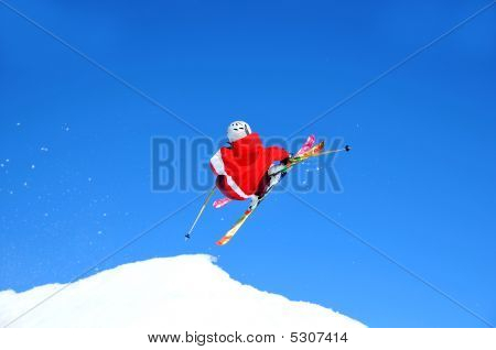 Skier In Red Taking Off On A Jump