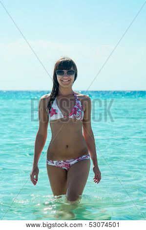 Joyous Slim Woman In Bikini Standing In Water With Sunglasses
