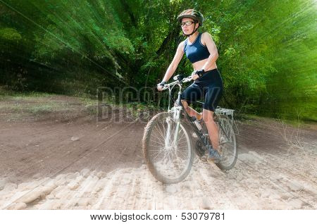 Female Cyclist rides through the forest with blur background