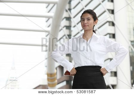 Portrait Of Young Businesswoman With Arms Akimbo