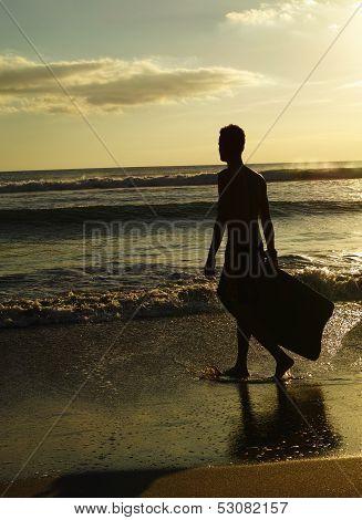 Surfer Walking On Beach