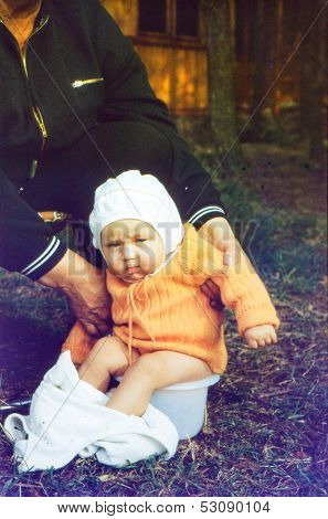 Vintage photo (scanned reversal film) - grandmother with baby granddaughter on potty, early eighties