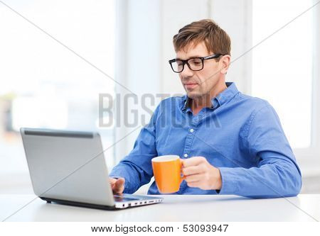 technology, business and lifestyle concept - man in eyeglasses working with laptop at home, holding a cup of warm tea or coffee