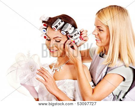 Woman with hair curlers on head wear in wedding dress .