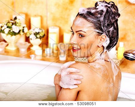 Yong woman washing hair in bubble bath.