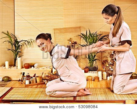 Therapist giving Thai stretching massage to woman.