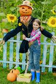 stock photo of scarecrow  - Scarecrow and happy girl  in the garden  - JPG