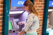 foto of cash  - Pretty brunette student withdrawing cash at an ATM - JPG