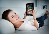 stock photo of tied hair  - Happy woman lying on couch and gambling on tablet at home in living room - JPG