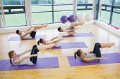 stock photo of physical exercise  - Class stretching on mats at yoga class in fitness studio - JPG