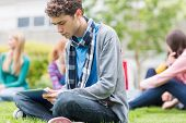 stock photo of down jacket  - Serious young college boy using tablet PC with blurred students sitting in the park - JPG