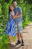 stock photo of amputee  - Confident smiling handicapped man wearing a prosthetic leg standing arm in arm with his pretty young girlfriend or wife on a leafy green rural path - JPG