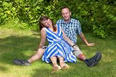 picture of amputee  - Happy attractive couple relaxing in the garden sitting close together on the grass with joyful friendly smiles  - JPG