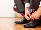 stock photo of black tie  - Man is tying his black shoes - JPG