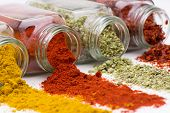 image of mixture  - Spice pouring out of set of spice jars close up    - JPG