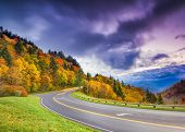 stock photo of tree lined street  - Winding road trough fall foliage overlooking the Smoky Mountains - JPG
