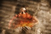stock photo of clairvoyant  - Mystic fire woman holding a burning oriental fan in a smokey haze of mystery and magic - JPG