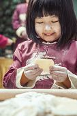 stock photo of medium-  length hair  - Portrait of little girl making dumplings in traditional clothing - JPG