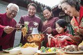 image of chopsticks  - Family enjoying Chinese meal in traditional Chinese clothing - JPG