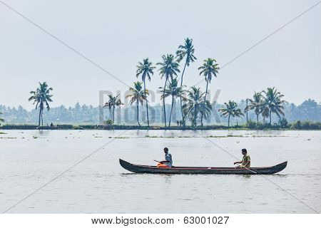 KERALA, INDIA - MAY 5, 2010: Unidentified indian men in small boat in backwaters. Kerala backwaters are both major tourist attraction and integral part of local people life in Kerala