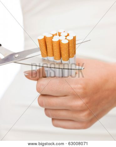 anti-smoking concept - close up of scissors cutting many cigarettes