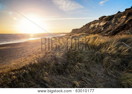Landscape Vivid Sunset Over Beach And Cliffs With Added Lens Flare Effect