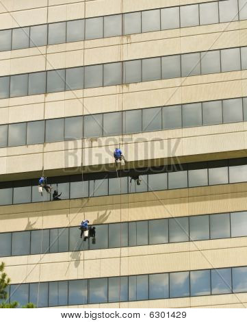 Three Window Washers Hanging On Ropes