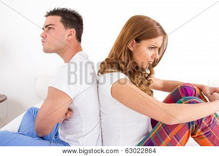 Couple Having An Argument While They Sitting On Bed