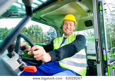 Builder or driver in construction machinery on building site