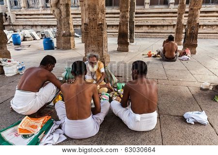 MADURAI, INDIA - FEBRUARY 16, 2013: Indian brahmin (traditional Hindu society) priest and pilgrims in famous Meenakshi Amman Temple - historic Hindu temple located in temple city Madurai