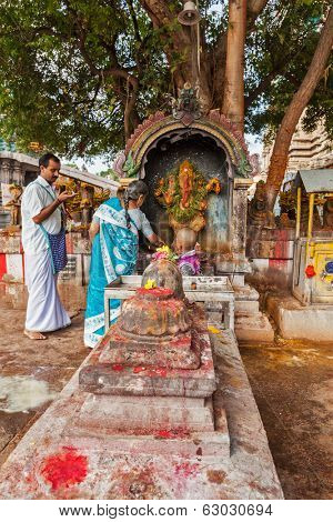 MADURAI, INDIA - FEBRUARY 16, 2013: Indian pilgrim family worshipping Hindu god Ganesh in famous Meenakshi Amman Temple - historic Hindu temple located in temple city Madurai