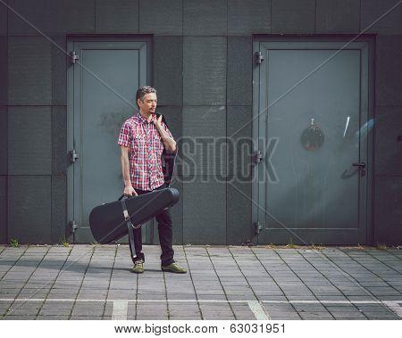 Man In Short Sleeve Shirt Holding Guitar Case