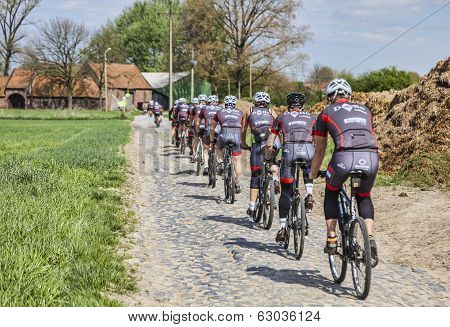 Amateur Cyclists On A Cobblestone Road