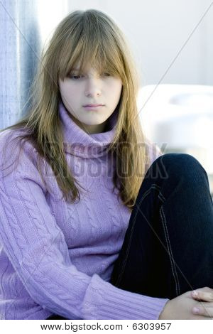 Young teenager girl sitting with her knee bent in sad depressed expression