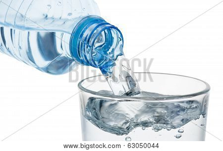 Pouring Glass Of Water From A Plastic Bottle Isolated On White Background