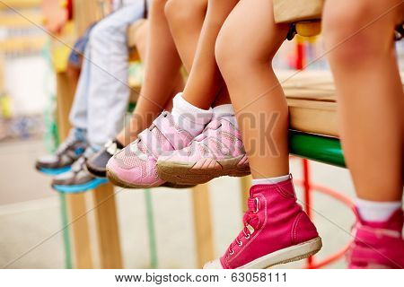 Legs of little friends sitting on swing or other recreational facility