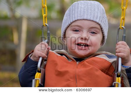 Toddler laughing on a swing.