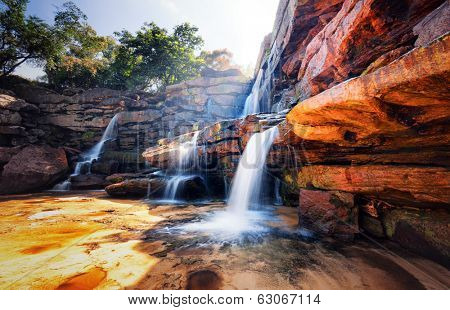 Waterfall and mountain landscape. Fresh water river stream flowing through beautiful rocky canyon. Nature photography