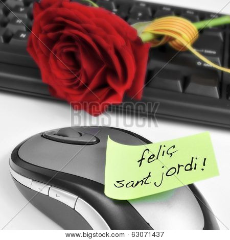 a red rose on a computer keyboard and the sentence felic Sant Jordi, happy Saint Georges Day, written in catalan in an sticky note
