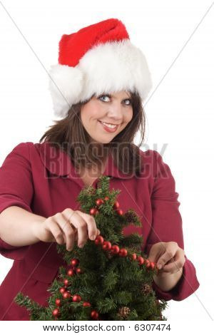 Young woman in Santa hat decorates a Christmas tree