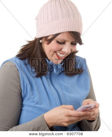 Young woman happily texting on her cell phone; isolated