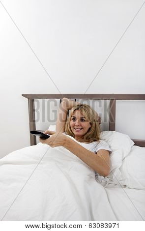 Happy young woman changing channels with remote control in bed